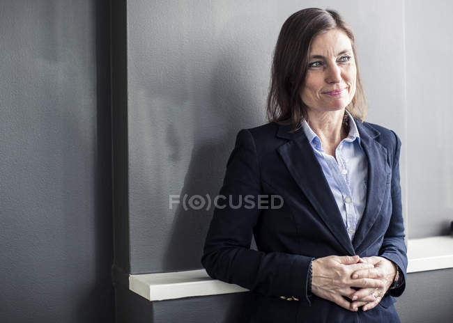 Thoughtful mature businesswoman with hands clasped looking away while leaning in office — Stock Photo