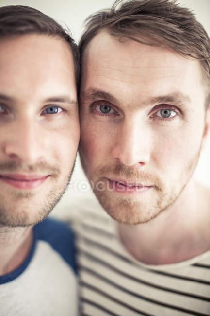 Retrato de cerca de pareja homosexual mejilla a mejilla - foto de stock