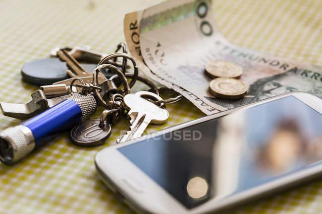 Teléfono inteligente con las llaves y dinero en mantel - foto de stock