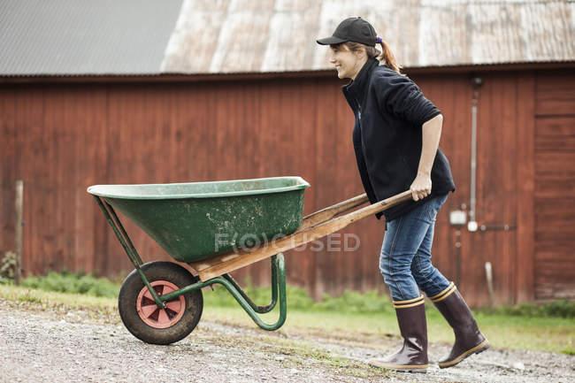 Самка - фермер їде на тачці по сільській дорозі. — стокове фото