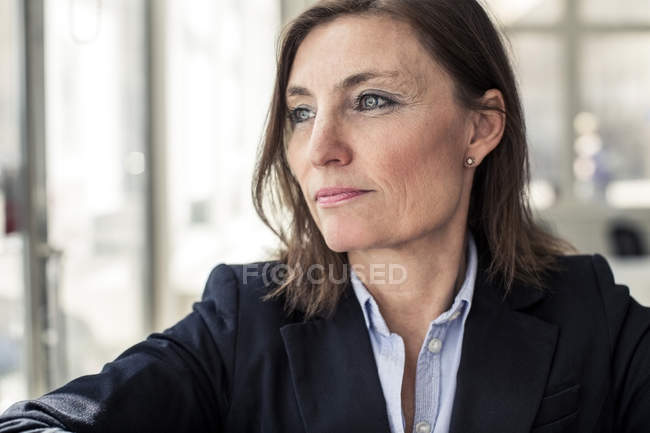 Thoughtful mature businesswoman looking away in office — Stock Photo