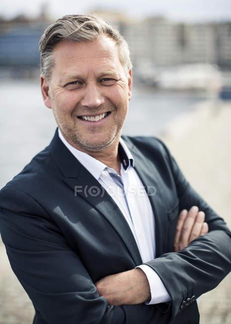 Porträt eines glücklichen Geschäftsmannes, der im Freien die Arme verschränkt — Stockfoto