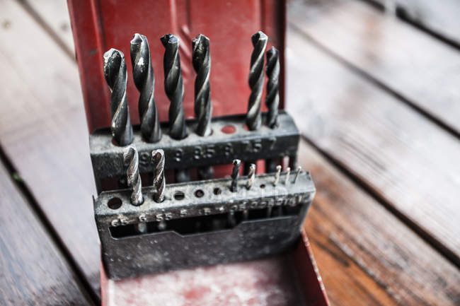 Variety of drill bits on wooden surface, close up — Stock Photo