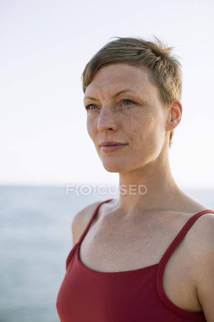 Продуманий жінка в спагетті скобами фотографіях хтось дивитися вбік проти моря — стокове фото