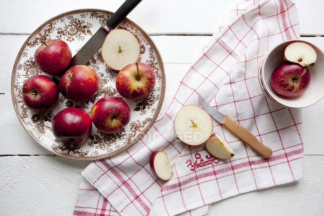 Directamente sobre la vista de manzanas frescas con servilleta y cuchillos de mesa - foto de stock