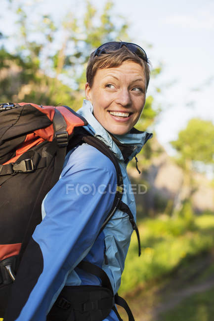 Female hiker with backpack looking over shoulder outdoors — Stock Photo