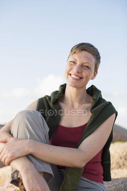 Retrato de mujer feliz relajándose en la roca contra el cielo despejado - foto de stock