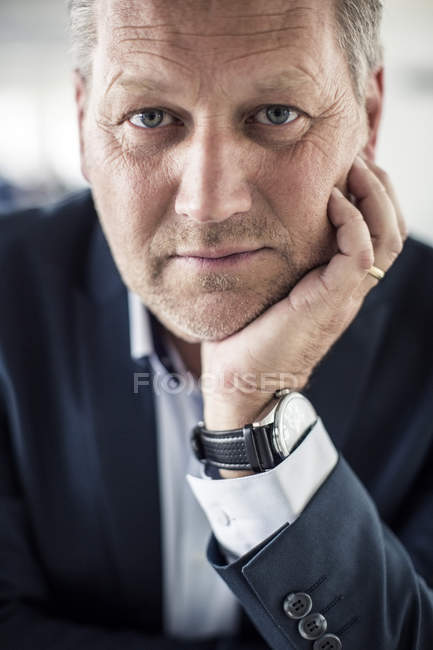 Portrait of confident businessman with hand on chin — Stock Photo