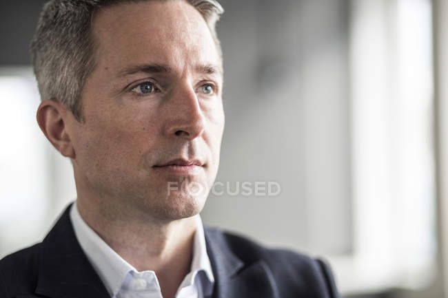Pensive maturo uomo d'affari guardando via in ufficio — Foto stock