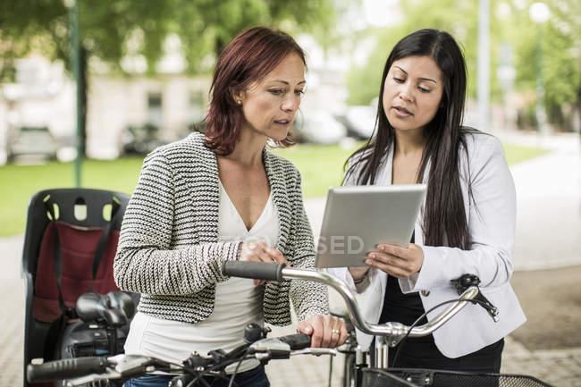Imprenditrici con biciclette che utilizzano tablet digitale su strada — Foto stock