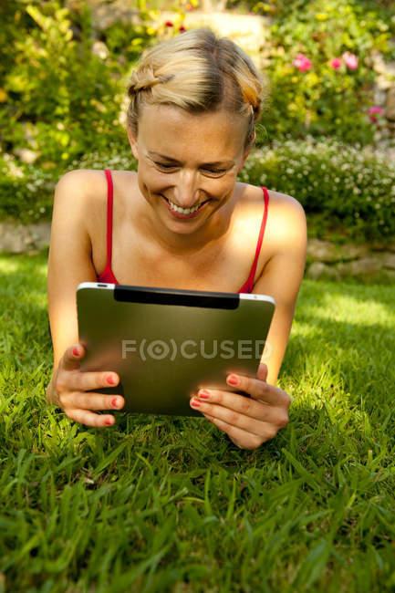 Mulher adulta média feliz usando tablet digital enquanto deitado na grama no parque — Fotografia de Stock