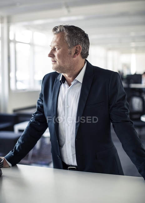 Thoughtful mature businessman looking away while standing at desk in office — Stock Photo