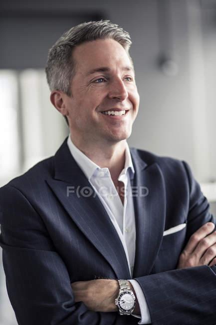 Вдумливий зрілий бізнесмен усміхнений, стоячи зброєю схрещеними в офісі — стокове фото