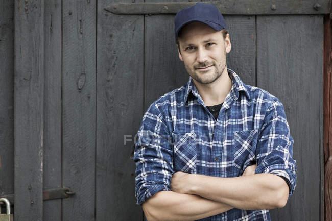 Retrato de agricultor confiante braços cruzados contra a porta do celeiro — Fotografia de Stock