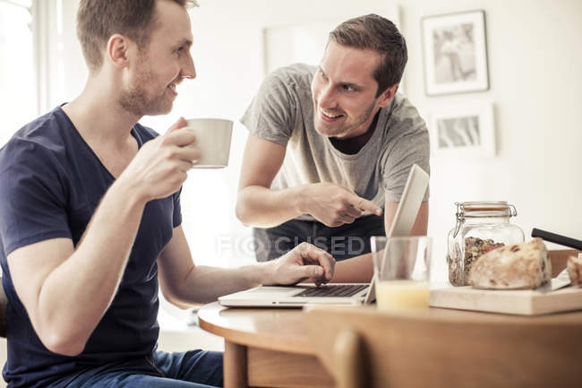 Homosexual couple using laptop together at breakfast table in home — Stock Photo