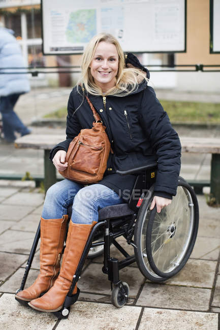 Portrait of happy disabled woman in wheelchair at bus stop — Stock Photo