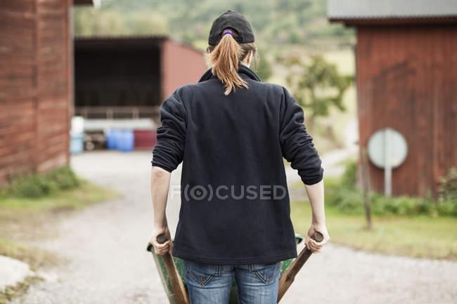 Передній вид фермера, який штовхає тачку по сільській дорозі. — стокове фото