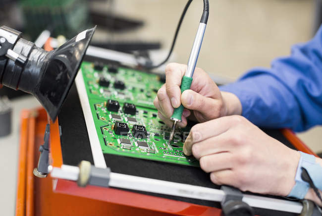Cropped image of electrician hand soldering circuit board — Stock Photo