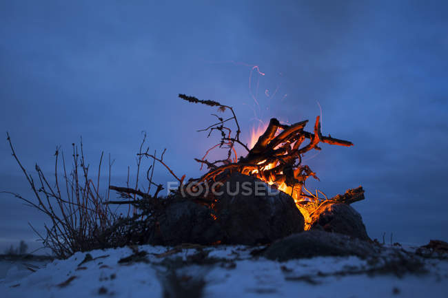 Bonfire burning in winter outdoors against blue sky in nighttime — Stock Photo
