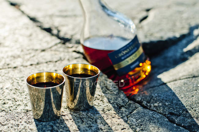 Close-up of two glasses and alcohol bottle — Stock Photo
