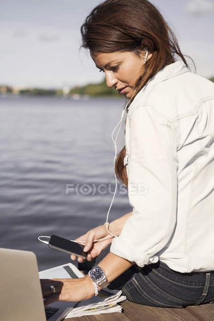 Empresária ouvindo música enquanto usa laptop no calçadão à beira-mar — Fotografia de Stock