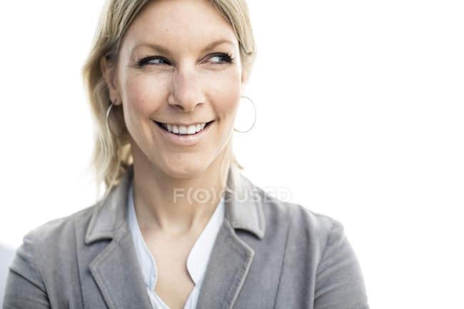 Mulher de negócios feliz que olha lateralmente ao estar de encontro à parede — Fotografia de Stock