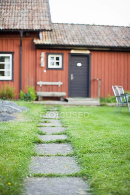 Fußweg auf grünem Rasen führt zum Haus — Stockfoto
