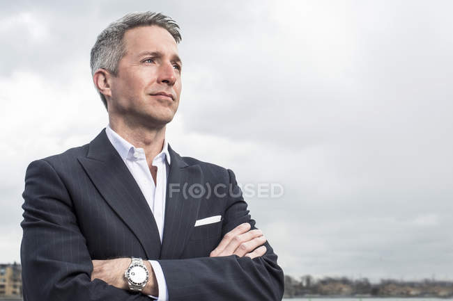 Thoughtful businessman looking away while standing arms crossed against cloudy sky — Stock Photo