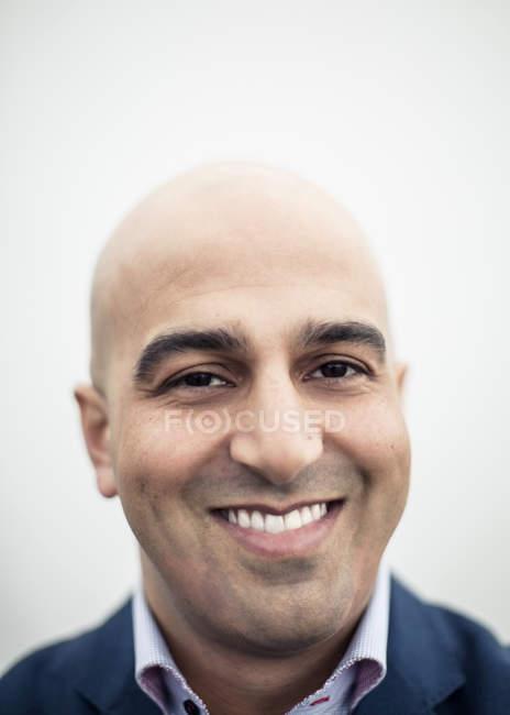 Portrait rapproché de milieu adulte d'homme d'affaires souriant contre le ciel clair — Photo de stock
