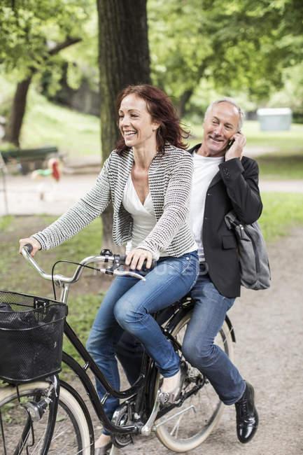 Бизнесмен ездит на велосипеде с коллегой по мобильному телефону на заднем сиденье — стоковое фото