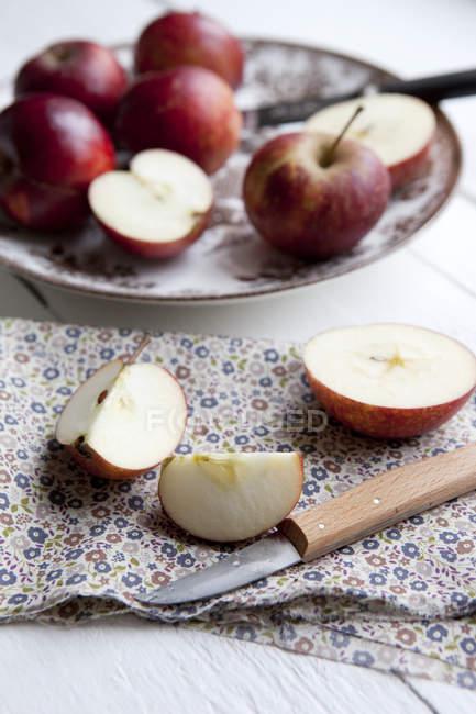 Vista de manzanas frescas picadas con servilleta y cuchillos de mesa - foto de stock