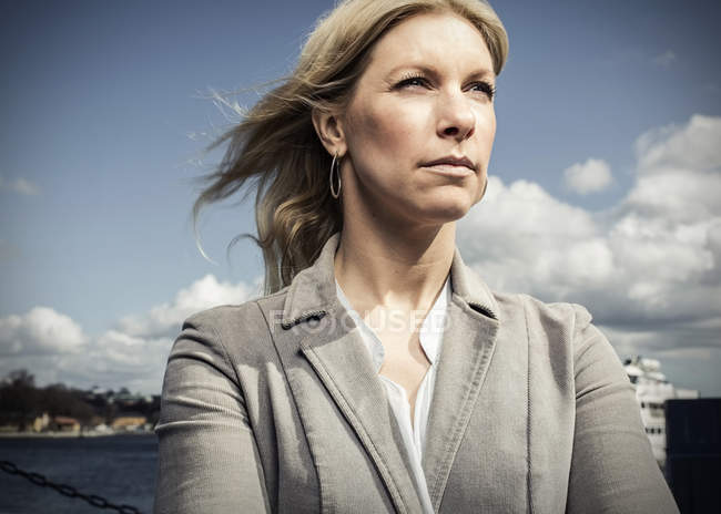 Thoughtful mid adult businesswoman looking away while standing against cloudy sky — Stock Photo