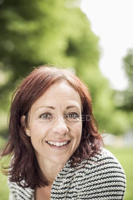 Retrato de mujer de negocios madura sonriendo en el parque - foto de stock