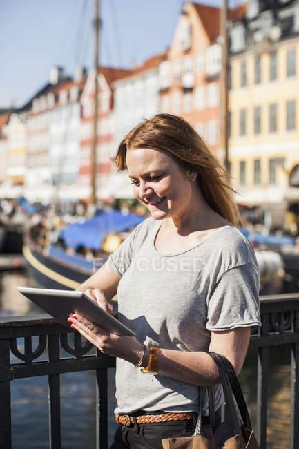 Mulher sorridente usando tablet digital por trilhos no porto — Fotografia de Stock