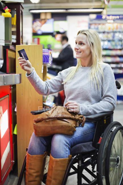 Behinderte Frau im Rollstuhl, die Zahlung per Kreditkarte im Supermarkt — Stockfoto