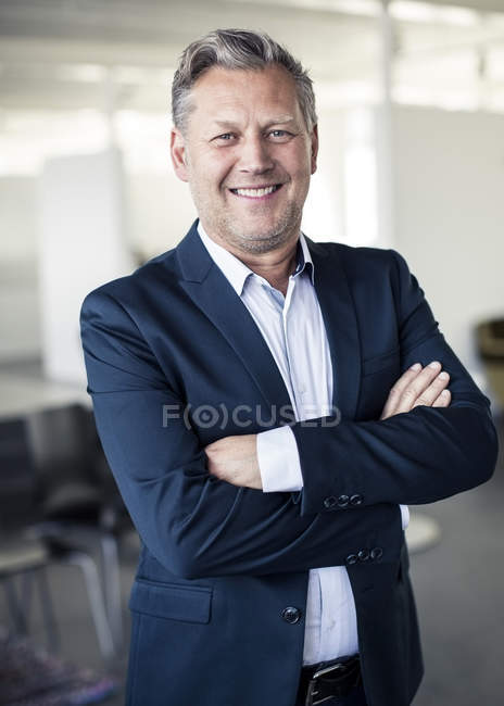 Portrait of happy mature businessman standing arms crossed in office — Stock Photo