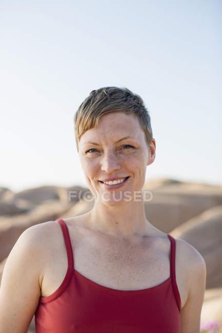 Портрет щасливі жінка в спагетті стропи стоячи проти порід — стокове фото