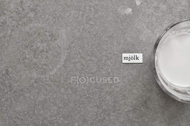 Tiro directamente encima de la leche de la etiqueta en idioma sueco por vaso de leche en la superficie gris - foto de stock