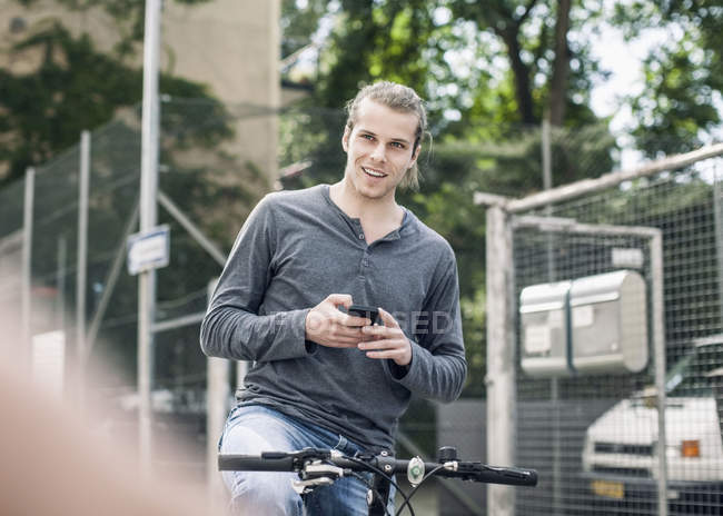 Smiling young man holding mobile phone sitting while on bicycle at street — Stock Photo