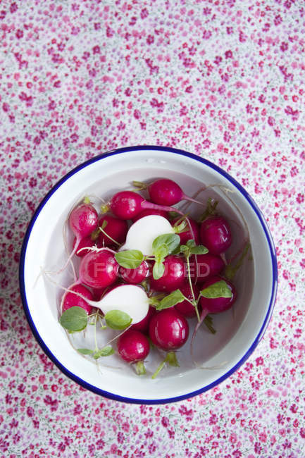 Directly above shot of fresh radishes in bowl on tablecloth — Stock Photo