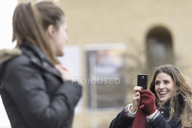 Happy woman photographing friend through mobile phone — Stock Photo