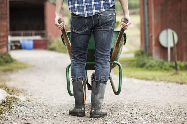 Низька ділянка фермера штовхає тачку на сільській дорозі. — стокове фото