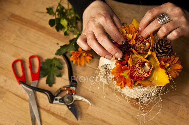 High angle view of female hands of florist creating floral arrangement — Stock Photo