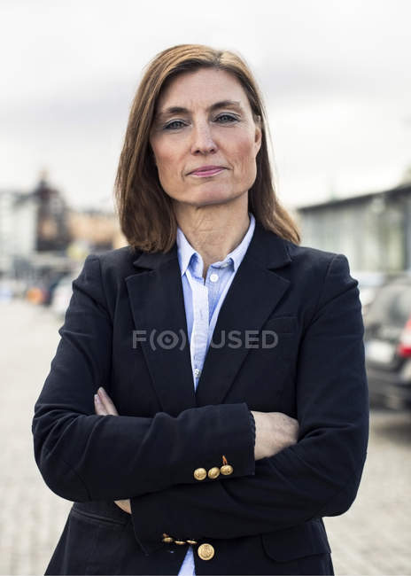 Portrait of confident mature businesswoman standing arms crossed on street — Stock Photo