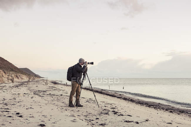 Full length side view of hiker photographing through SLR camera on shore at beach — Stock Photo