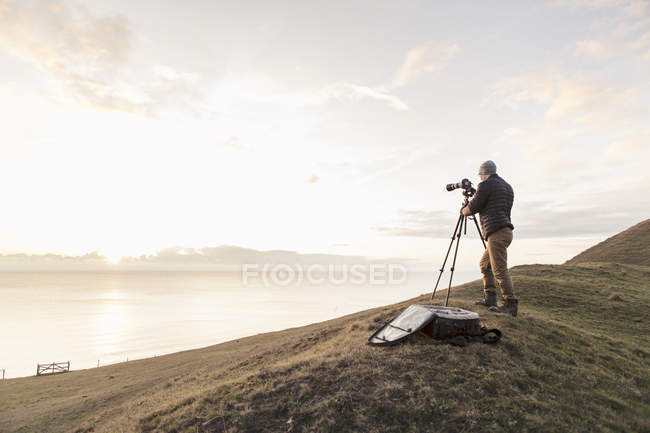 Rear view of hiker photographing sea through SLR camera while standing on hill — Stock Photo