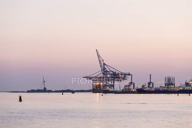 Cranes by river against sky during sunset — Stock Photo
