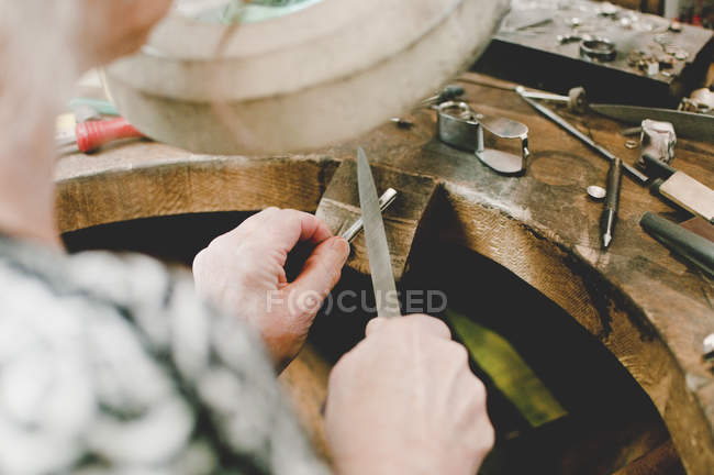 High angle view of senior female jeweler working at workbench in workshop — Fotografia de Stock