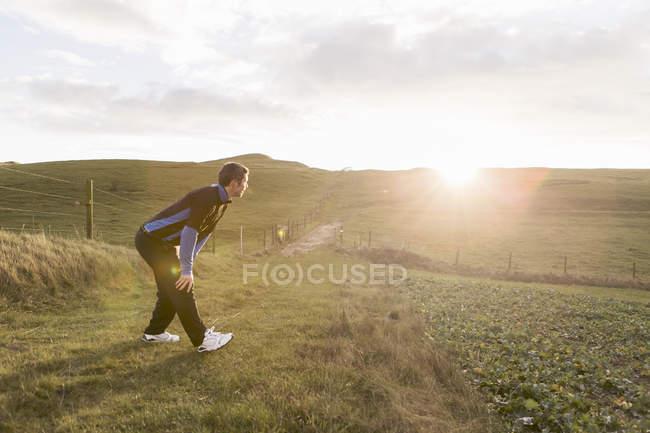 Seitenansicht eines müden sportlichen Mannes, der bei sonnigem Wetter mit der Hand auf dem Knie auf dem Feld steht — Stockfoto