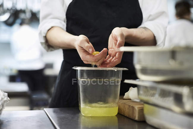 Midsection of chef separating egg yolk from whites in commercial kitchen — Stock Photo